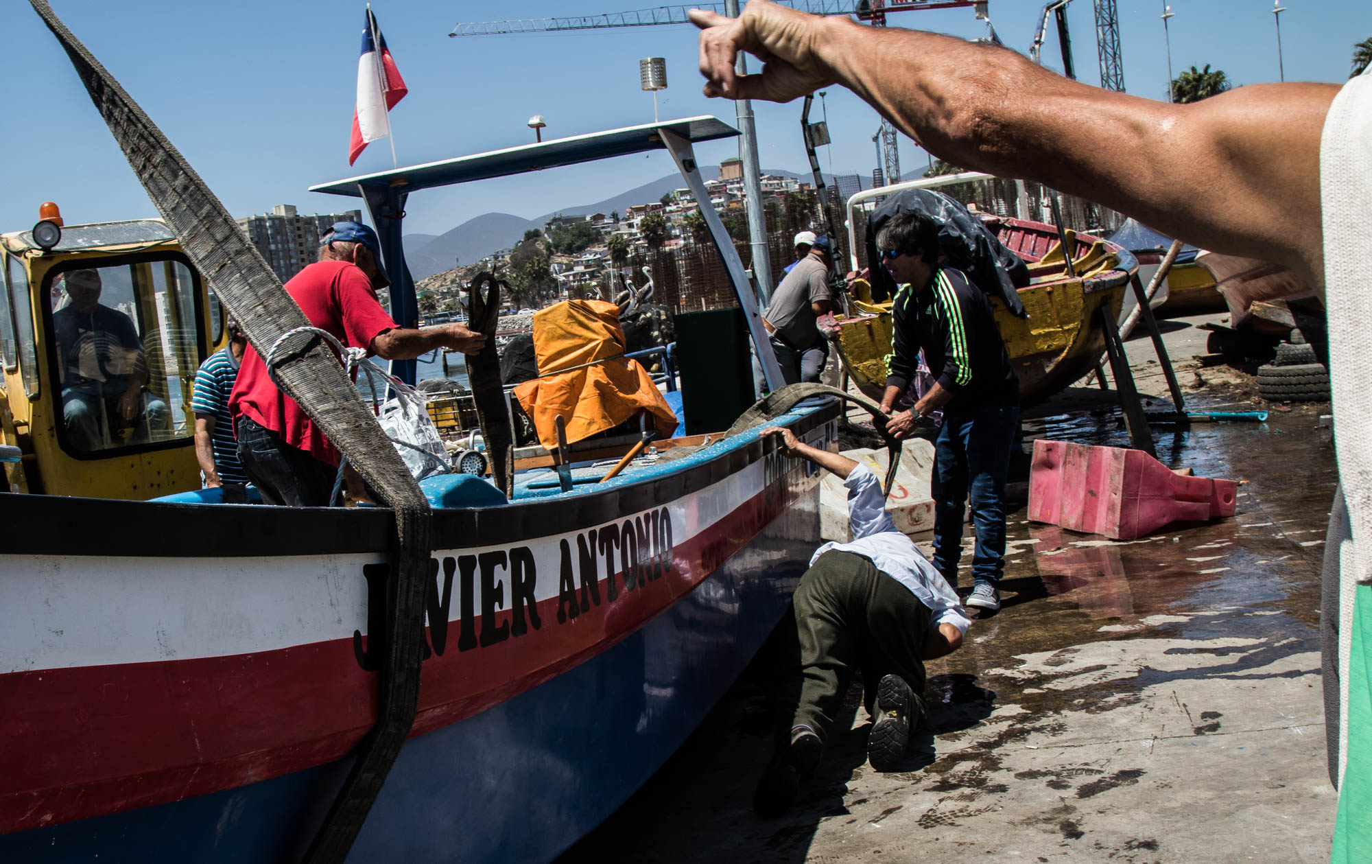 "Local fishermen gather at the Coquimbo port to help place a rebuilt boat back into the water. The ship was damaged in the tsunami of 2015 and took one year to repair. Hundreds more boats were damaged in the tsunami which has also lead to the shrinking of the fishing industry since the fishermen don't have a way to go out in the water and fish like they used to be able to. A local fishermen and restaurant owner in the market nearby, Harry Gloria relives the night of the tsunami. ""Last September, around 8 o'clock, there was an earthquake. After the earthquake, about 25 minutes later, there came a tsunami. It was about 4-5 waves but they were 5 meters large each…about 4-5 waves. By midnight, it had destroyed everything around here in Coquimbo, the whole coast was destroyed, the inlet of Coquimbo was all destroyed."""